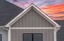 White Frame Gutter Guard System, With Dark Gray Horizontal Vinyl Siding, White Accents, Fascia, Soffit, On A Pitched Roof Attic At A Luxury American Single Family Home Dramatic Colorful Sunset Sky