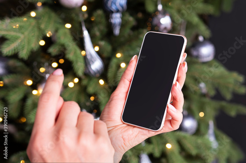 Fototapeta Smartphone in a woman's hand on the background of a Christmas tree