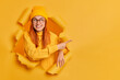Leinwandbild Motiv Good looking cheerful millennial girl with tender smiles advertises something suggests discounts indicates at blank space dressed in casual jumper and hat poses in ripped hole of yellow background