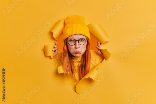 Obraz Unhappy disappointed young woman purses lips and looks sadly at camera stands offended breaks through paper background against yellow background. Upset gloomy redhead teenage girl in spectacles - fototapety do salonu