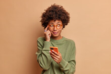 Pensive Dark Skinned Young Ethnic Woman Keeps Index Finger On Temple Tries To Remember Telephone Number Of Someone Holds Modern Smartphone And Concentrated Aside Wears Glasses Casual Jumper.