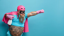 Horizontal Shot Of Self Confident Male Hero Wears Pink Helmet Cloak And Rubber Gloves Holds Bottle Of Detergent Ready To Help You With Cleaning Stretches Arm As Going To Fly Isolated Over Blue Wall