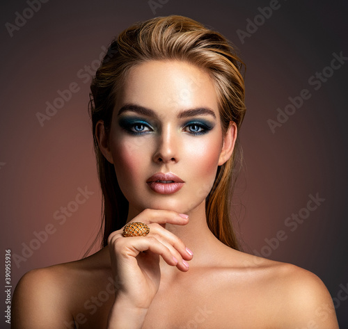 Photo of young woman with style make-up. Portrait of blonde woman with a beautiful face. Closeup face with stylish blue makeup. Fashion model with long hair, studio shot.