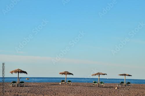 Fototapeta Closeup shot of sun loungers and umbrellas on a sandy beach  in the Canary Islan