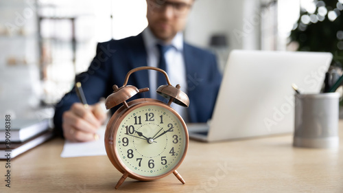 Obraz Focus on clock standing on table with busy young businessman entrepreneur in formal wear on background, focused millennial male manager involved in casual working process, time management concept. - fototapety do salonu