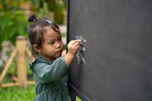 Cute Little Girl Writing Alpha...