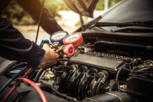Close Up Hand Of Auto Mechanic Are To Use Manifold Gauge Is Measuring Equipment For Filling Car Air Conditioners. Concepts Of Car Care Fix Checking Repair Service And Insurance.