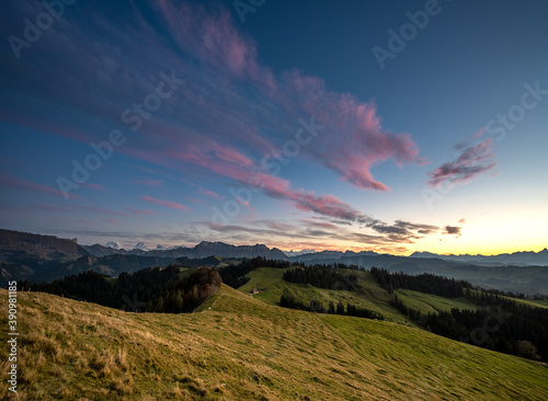 Fototapeta overview swiss landscape with hills forests mountains in warm color during sunse