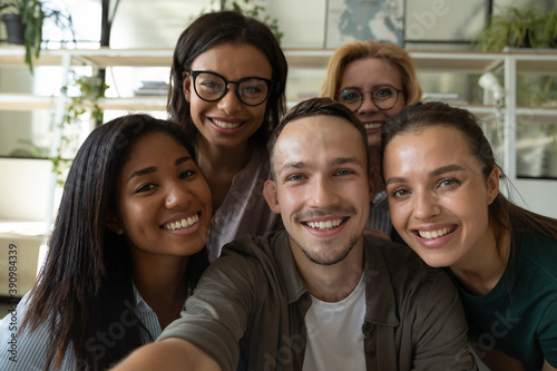 Obraz Happy laughing team diverse colleagues posing for selfie portrait in office, friendly group of corporate employees of different age and ethnicities making videocall looking at camera bonding together - fototapety do salonu