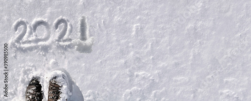 top view on 2020 hand writing on the snow with hiker foot in panoramic size Fotobehang