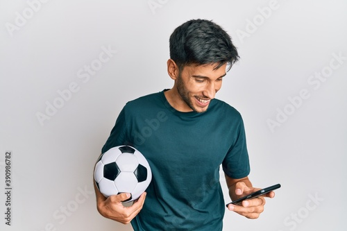Foto Young handsome man holding football ball looking at smartphone bet app smiling and laughing hard out loud because funny crazy joke