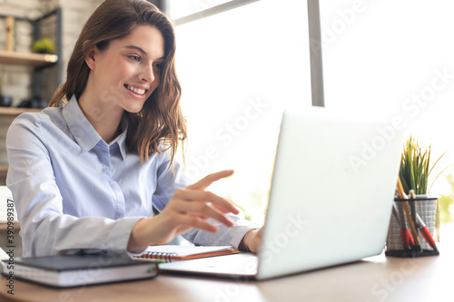 Smiling pretty woman sitting at table, looking at laptop screen. Happy entrepreneur reading message email with good news, chatting with clients online.