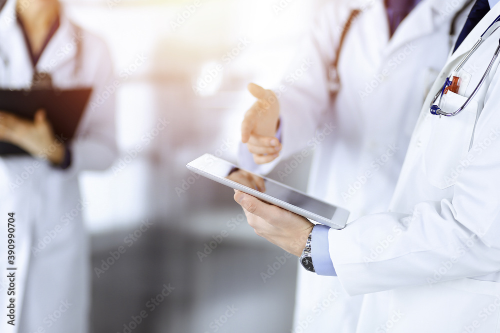 Leinwandbild Motiv - rogerphoto : Group of unknown doctors use a computer tablet to check up some medical names records, while standing in a sunny hospital office. Physicians ready to examine and help patients. Medical help, insurance