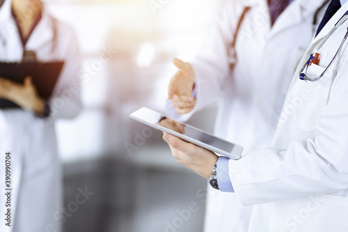Group of unknown doctors use a computer tablet to check up some medical names records, while standing in a sunny hospital office. Physicians ready to examine and help patients. Medical help, insurance