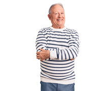 Senior Handsome Grey-haired Man Wearing Casual Striped Sweater Happy Face Smiling With Crossed Arms Looking At The Camera. Positive Person.