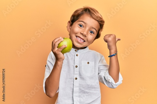 Obraz Adorable latin kid holding green apple pointing thumb up to the side smiling happy with open mouth - fototapety do salonu