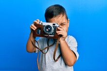 Adorable Latin Photographer Toddler Smiling Happy Using Vintage Camera Over Isolated Blue Background.