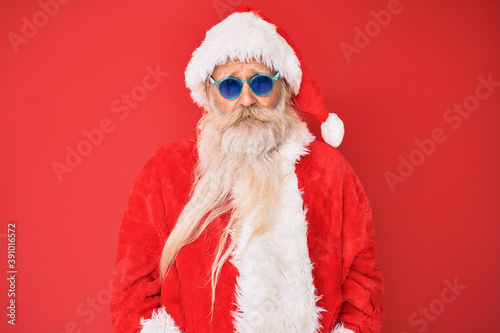 Canvastavla Old senior man wearing santa claus costume and sunglasses with serious expression on face