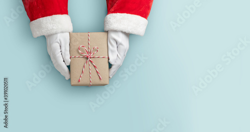 Foto Top view of Santa claus hands is holding a brown gift box or present box over blue isolated background