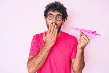 Handsome Young Man With Curly Hair And Bear Holding Paper Airplane Covering Mouth With Hand, Shocked And Afraid For Mistake. Surprised Expression