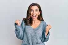 Young Brunette Woman Wearing Casual Winter Sweater Celebrating Surprised And Amazed For Success With Arms Raised And Open Eyes. Winner Concept.