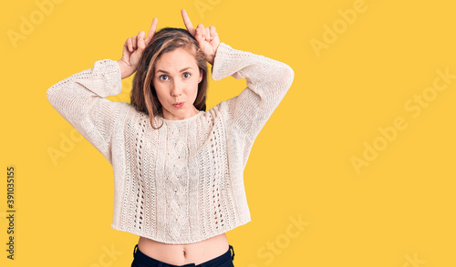 Fotografiet Young beautiful blonde woman wearing casual sweater doing funny gesture with fin
