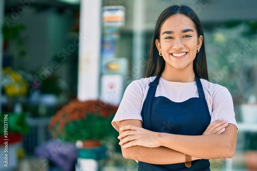 Young latin shopkeeper girl with arms crossed smiling happy standing at the flor Poster Mural XXL
