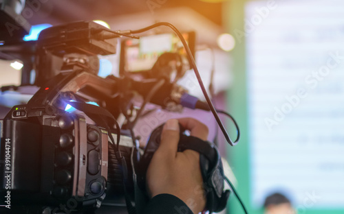 Rear side the scene of video camera recording event shooting conference hall live streming wifi microphone sending for presentation with light studio background Fotobehang