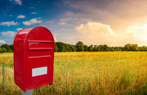 Fotografie, Tablou Big red cozy postbox with white empty note space for address is standing outdoor in front of beautiful countryside landscape at sunset background with farm field and poppies flowers