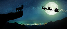 Silhouette Of Reindeer Standing On The Cliff To See Santa Claus Flying On Their Reindeer Over The Full Moon At Night Christmas.