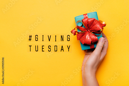 Fototapeta Giving Tuesday. Global day of charitable giving after Black Friday shopping day. Woman hand holding gift box on yellow background obraz