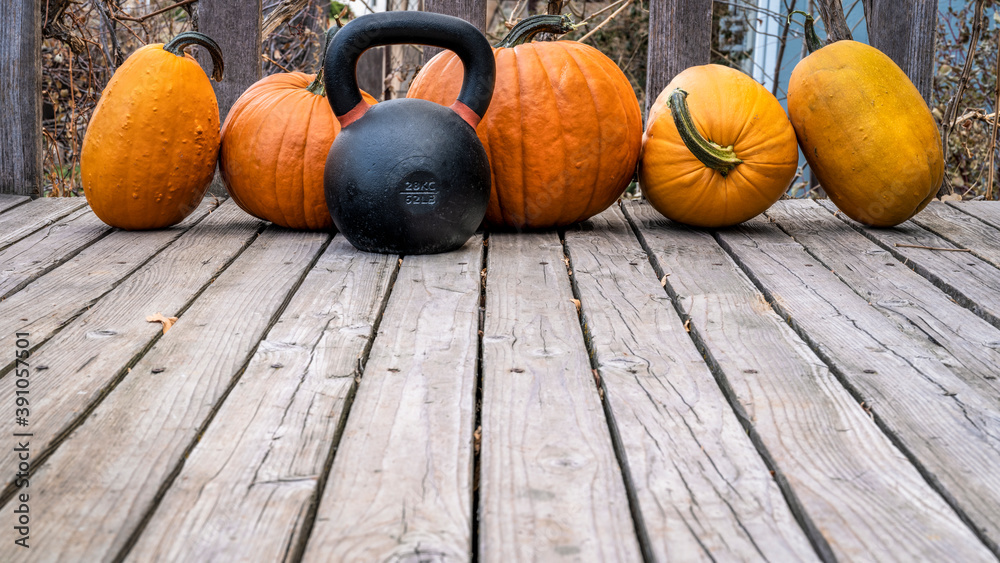 Fototapeta heavy iron kettlebell with a crop of pumpkins on a wooden deck, fall holidays and fitness concept