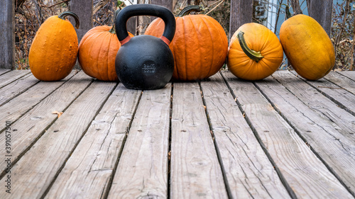 Fototapeta premium heavy iron kettlebell with a crop of pumpkins on a wooden deck, fall holidays and fitness concept