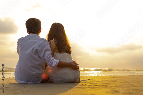 Foto Couple in love watching sunset together on the beach travel summer holidays