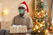 Leinwandbild Motiv Waist up portrait of smiling African-American man holding Christmas gift and wearing mask while posing in cozy home interior, copy space