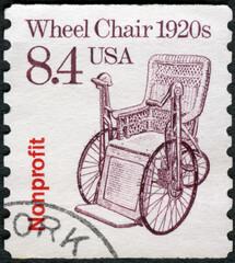 Fototapeta na wymiar USA - 1987: shows Wheel Chair 1920s, series Transportation Coils series, 1987