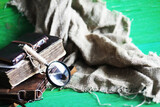 Fototapeta Kawa jest smaczna - Old leather bag with a magnifying glass on a brown traveler wooden table background with copy space.