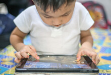 Little Kid's Using Digital Touchscreen Phone Tablet Computer Playing Games.