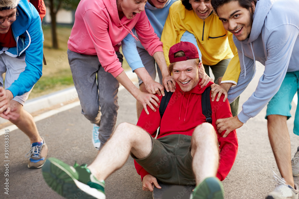 Fototapeta modern friendly guys in casual clothes skateboarding and showing exciting tricks, in the park, city life. extreme sport concept