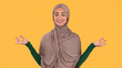 Muslim Woman In Hijab Meditating With Eyes Closed, Yellow Background