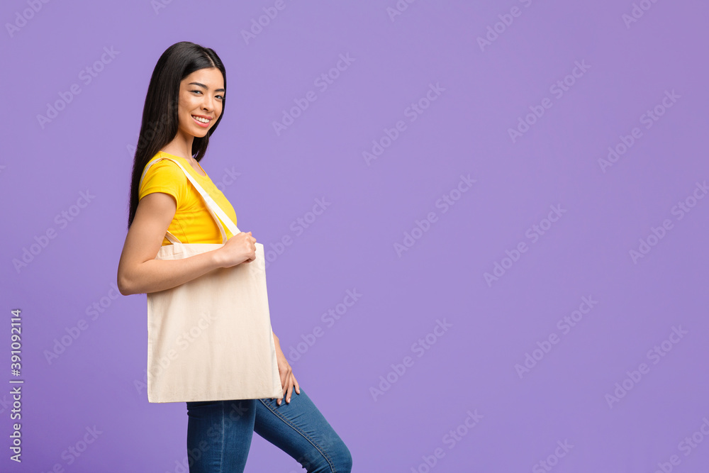Fototapeta Young Asian Woman With Blank Tote Canvas Shopping Bag Posing Over Purple Background