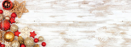 Fototapeta Christmas corner border of red and gold ornaments. Above view on a white rustic white wood banner background. Copy space. obraz