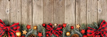 Christmas Bottom Border Of Ornaments, Branches And Buffalo Plaid Check Ribbon. Top View On An Old Wood Banner Background.