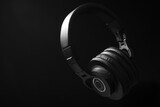 Black professional headphones on a black background. Musical production. Sound studio equipment. Sound engineer working tool. Closed-back Headphones for music lovers. Black on black.  Low key photo.