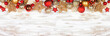 Christmas top border of red and gold ornaments. Overhead view on a white rustic white wood banner background. Copy space.