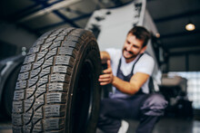 Hardworking Experienced Worker Holding Tire And He Wants To Change It. In Background Is Truck. Selective Focus On Tire.