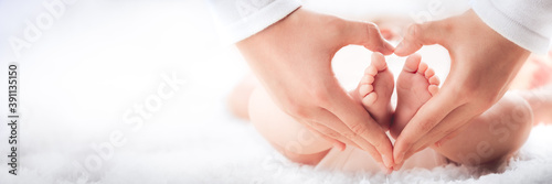 Mother Holding Baby's Feet In Heart Shaped Hands - Infant Care Concept #391135150