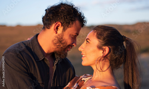Fototapeta A romantic and lovely latin couple looking each other with love after a kiss in
