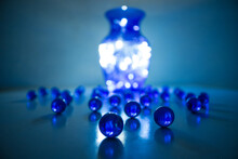 Magic Scene Of A Blue Crystal Vase And Many Blue Marbles