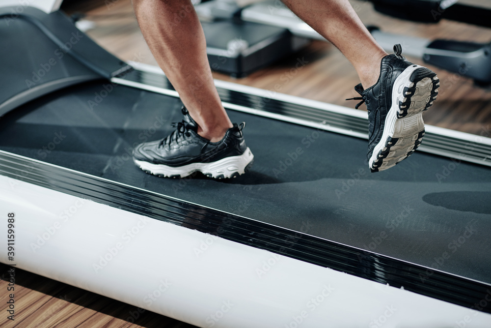 Fototapeta Close-up image of fit man in sneakers running fast on treadmill in gym in the morning